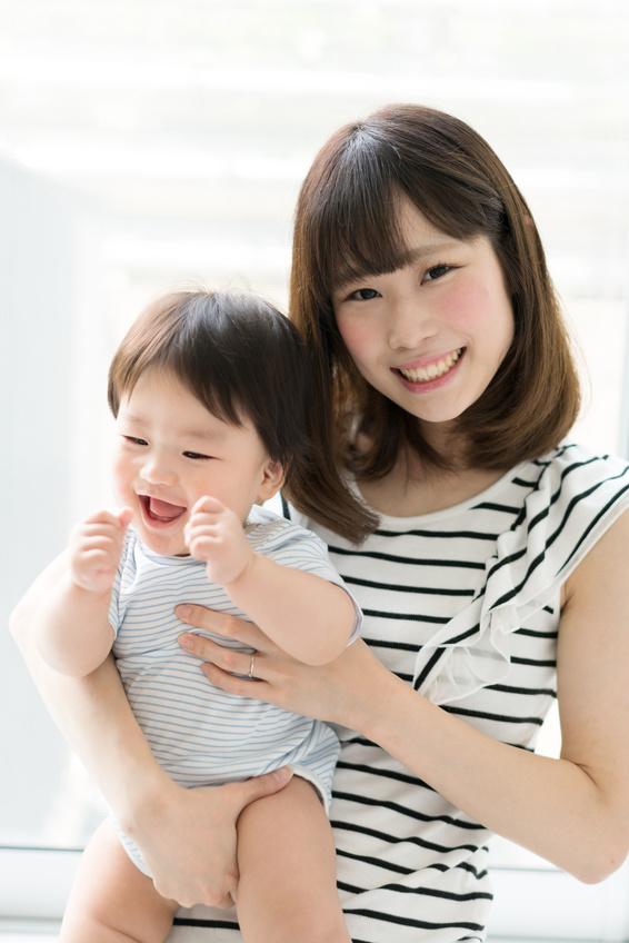 赤ちゃんを抱っこする笑顔のママ
